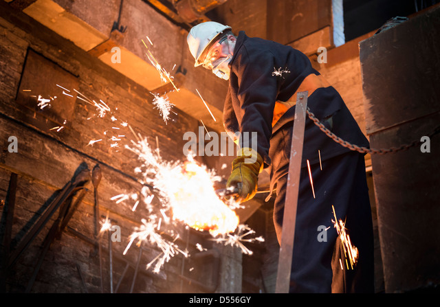 Worker cleaning mould in metal foundry - Stock Image