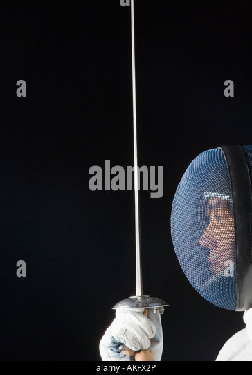 Close-up of a male fencer holding a fencing foil - Stock Image