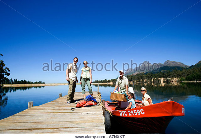 Multi generational family loading motorboat with provisions at lake jetty grandfather holding picnic hamper - Stock-Bilder