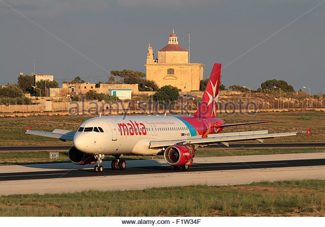 Commercial air travel. Air Malta Airbus A320 jet plane on arrival in Malta, with Ta' Loretu Chapel, outskirts - Stock-Bilder