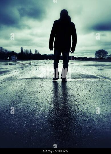 Rear view silhouette of a mysterious male figure walking outdoors - Stock Image