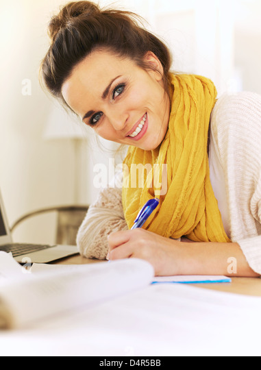 Closeup of a cheerful woman writing something in her journal - Stock Image