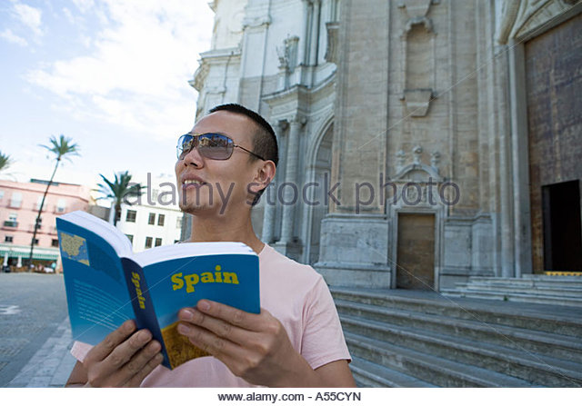 Man holding tour guide - Stock Image