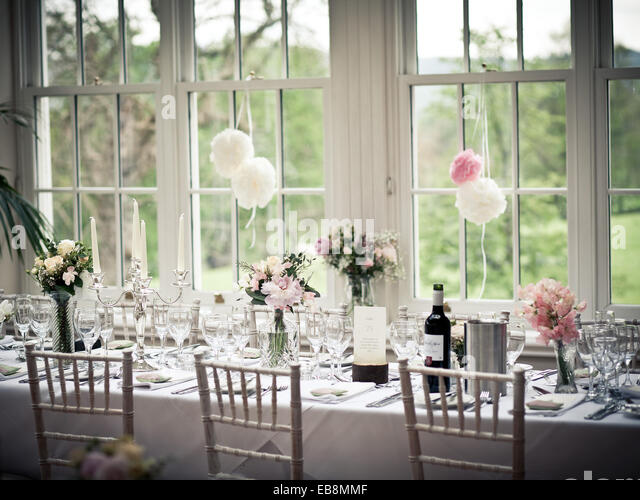 wedding breakfast top table settings with flowers and wine - Stock Image