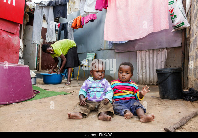 South Africa African Johannesburg Soweto Black woman mother boy son baby home dirt floor - Stock Image