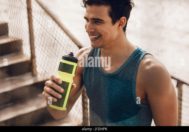 Athlete resting after running with bottle of water. Rest after a hard workout at beach. - Stock Image