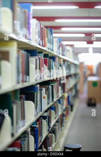 Books on bookshelves in library - Stock Image