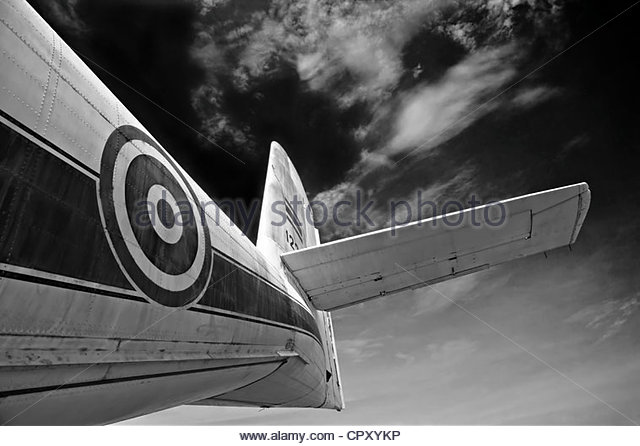 Black and white monotone image of an airplane wing and fuselage against a dark sky. - Stock Image