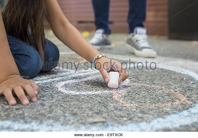 Girl drawing hopscotch number 8 with sidewalk chalk - Stock-Bilder