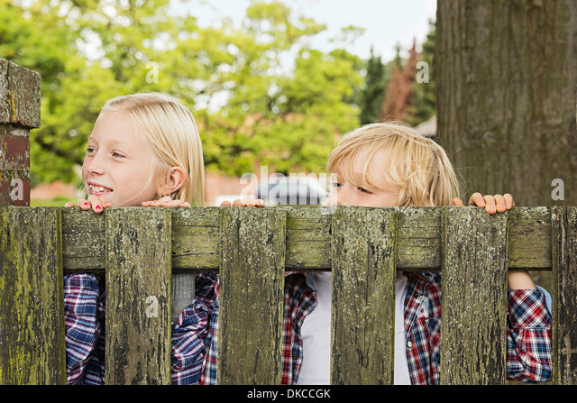 Brother and sister peering over wooden gate - Stock Image