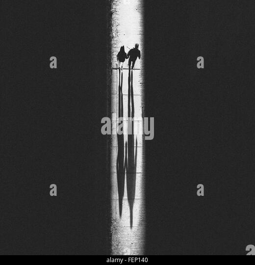 Two People Walking On Glowing Footpath - Stock Image