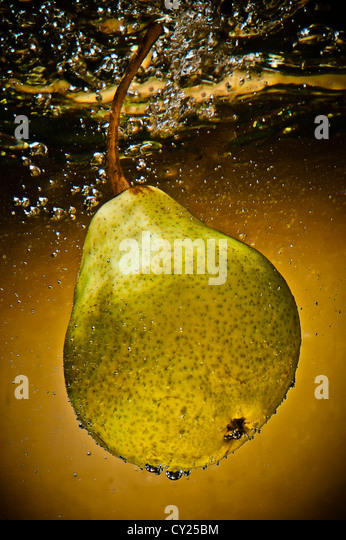 Creative image of a Pear in water against a Gold background. - Stock Image