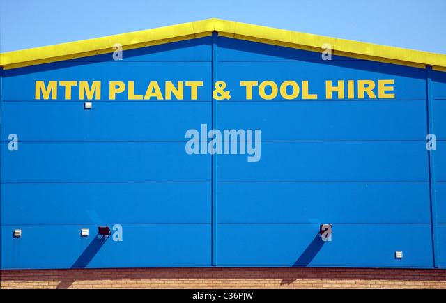 Yellow and blue graphic design pattern on industrial building MTM Plant and Tool Hire company Sudbury Suffolk England - Stock Image