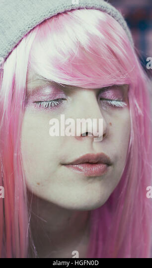 Portrait of a young woman with pink hair and her eyes closed like she's dreaming - Stock Image