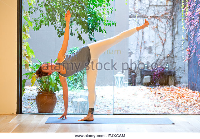 Woman Practicing Yoga, Half-moon pose - Stock Image
