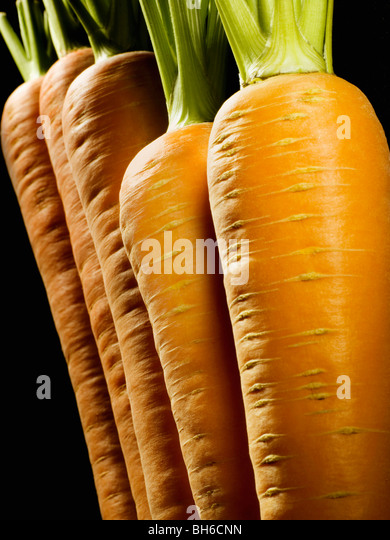 A cropped shot of a line of carrots - Stock Image