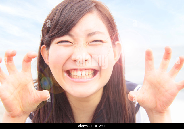 Young woman pulling funny face and hands like claws - Stock Image