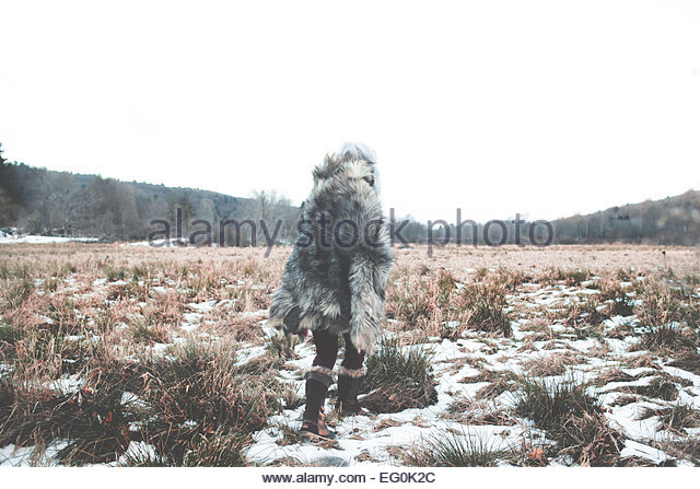 Woman wearing fur coat walking away across snowy grassland - Stock Image