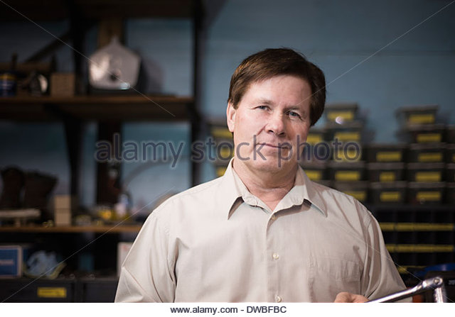 Senior man standing in workshop - Stock Image