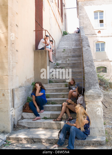 A flight of old stone steps with seven young women sitting on them, Arles, France - Stock Image
