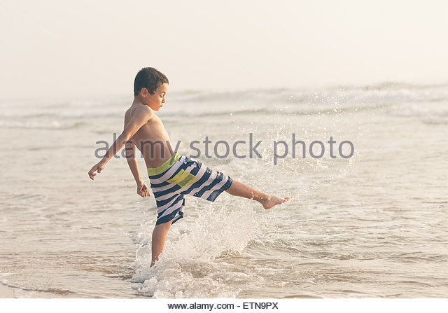 Boy on the beach splashing in the surf - Stock Image