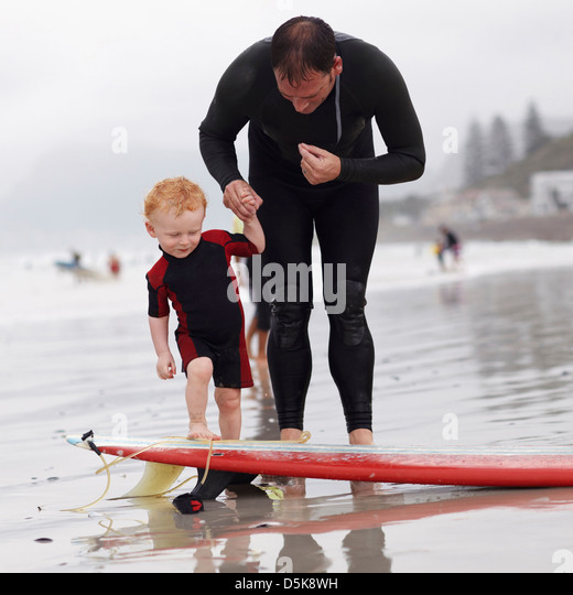 Father and his son (2-3) on beach by surfboard - Stock-Bilder