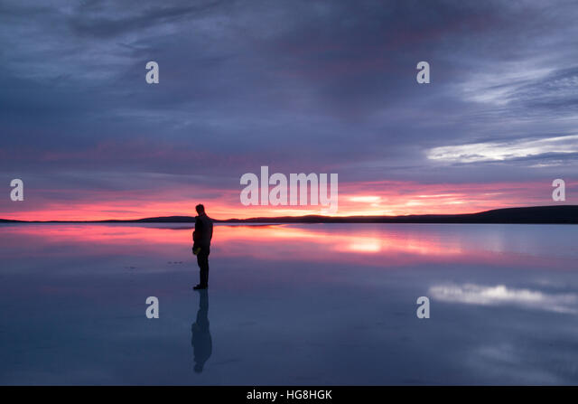 A silhouette of a man stands on a reflective lake in sunset or sunrise. - Stock Image