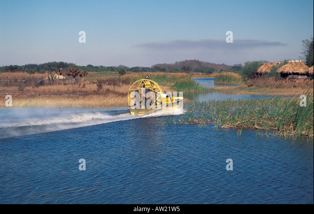 Fast yellow airboat speeds past Seminole Indian old style thatch chickee dwelling everglades florida - Stock Image