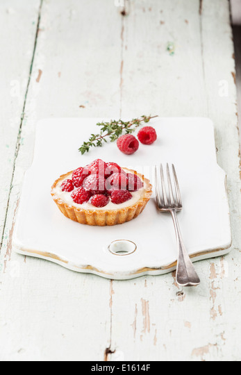 Tartlet with fresh raspberries and fork - Stock Image