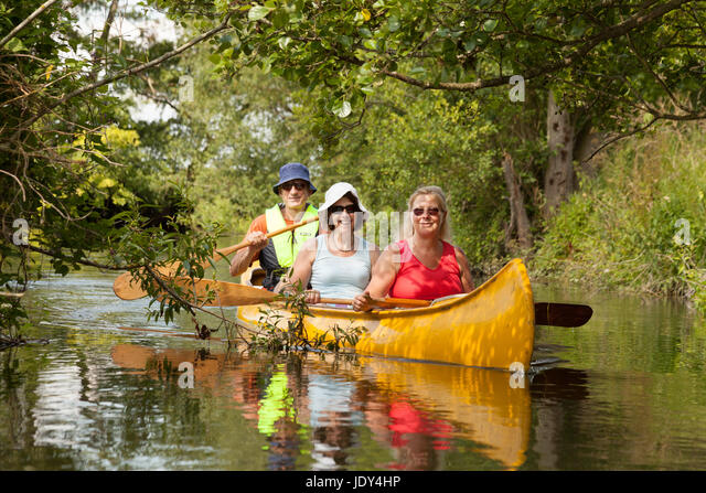 Three people in a canoe, canoeing on the river Lodden, Oxfordshire England UK - Stock Image