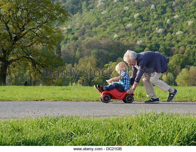 Grandmother pushing boy on go kart - Stock-Bilder