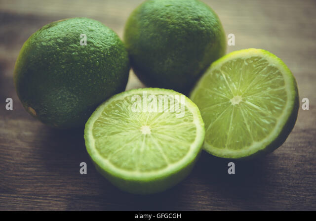 Still life of limes on wood table top. - Stock Image