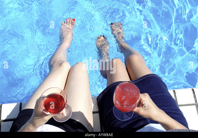 Two women sitting on the pool side with cold beverages - Stock-Bilder