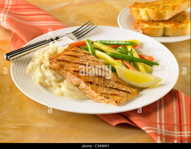 Salmon dinner served with mashed potatoes and vegetables - Stock Image