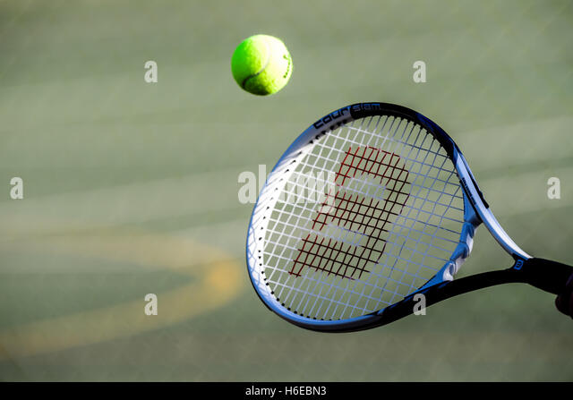 Tennis ball hitting a racket - Stock-Bilder