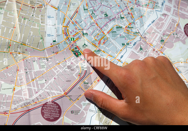 Young man pointing at the Tivoli Gardens in central Copenhagen on a tourist city map of Copenhagen, Denmark. - Stock Image