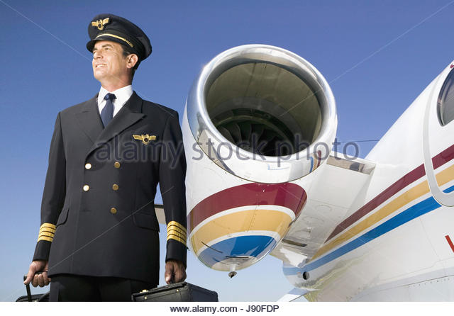 Pilot Of Private Jet Standing By Engine Of Plane - Stock-Bilder