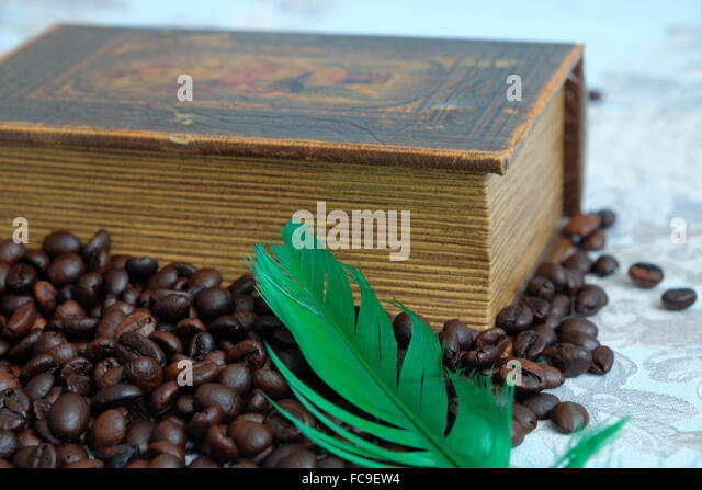 Roasted coffee beans, old book and a green pen - Stock Image