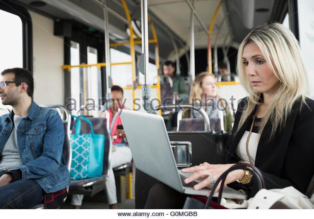 Businesswoman using laptop on bus - Stock Image