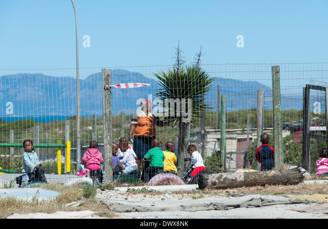 Children and teacher playing outside a Kindergarten in Khayelitsha, Cape Town, Western Cape, South Africa - Stock Image