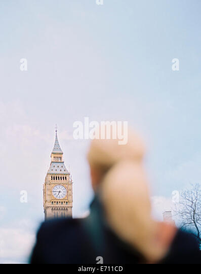 A woman looking up at Big Ben, The Elizabeth Tower at the Houses of Parliament in London. - Stock-Bilder