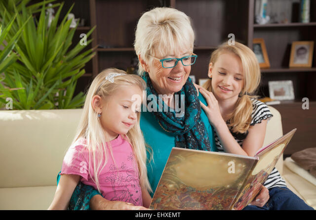 Grandmother reading book to her granddaughters, Bavaria, Germany - Stock-Bilder