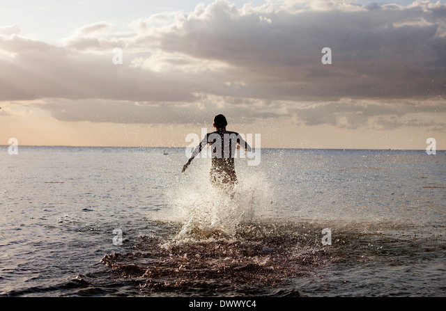 Rear view of man running in sea - Stock Image