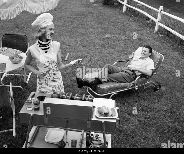 1950s 1960s WOMAN IN CHEF'S HAT AND APRON GRILLING HOT DOGS ON GRILL MAN IN CHAISE LONGUE LAUGHING EATING A - Stock-Bilder