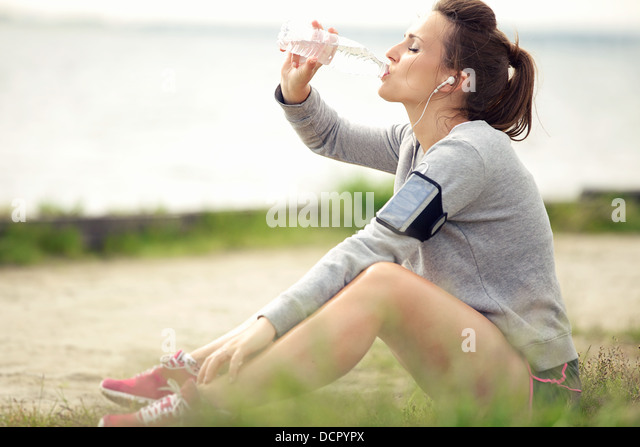 Tired female jogger sitting on the grass and drinking bottled water - Stock Image