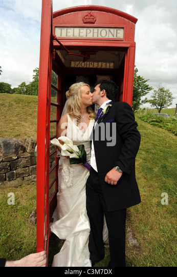 British traditional bride and groom kiss in a traditional red phone box on their wedding day - Stock-Bilder