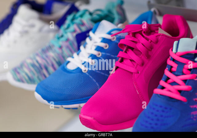 Variety of the colorful sneakers in the shop - Stock Image
