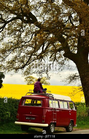 Oswestry, Shropshire, UK. 16th April, 2017. A woman with her classic red Volkswagen T2 campervan gazes over a field - Stock Image