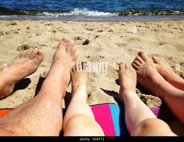 Legs of family relaxing on the beach - Stock Image