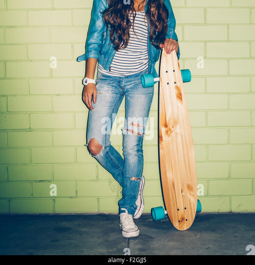 beautiful long-haired girl with wooden longboard skateboard stand near the green brick wall - Stock-Bilder
